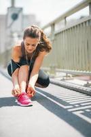 fitness ung kvinna som knyter skosnören i staden foto