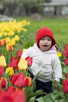 bedårande barnflicka som samlar tulpaner foto