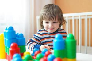 barn pojke spelar plast block foto