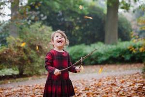 småbarn tjej i tartan klänning leker med blad och pinnar foto