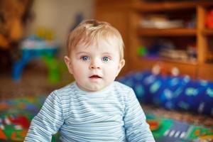 liten baby som leker med olika leksaker inomhus foto