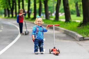 två barnpojke och flicka som rider på skotrar i staden