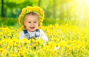 glad baby flicka i krans på ängen med gula blommor