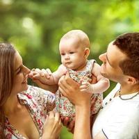 föräldrar med baby i park foto