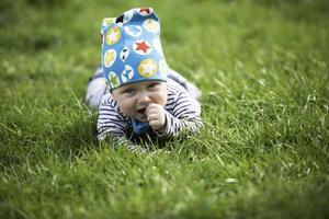 baby som lägger sig på gräset foto