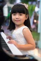 liten flicka som bär vit klänning och spelar piano foto
