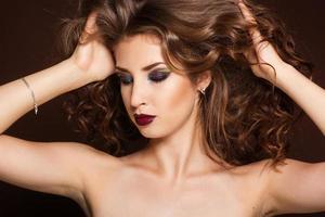 vacker brunett tjej med friskt lockigt hår foto