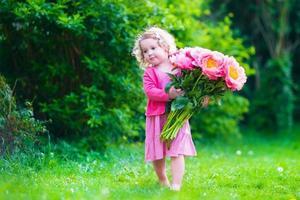 bedårande liten flicka med pionblommor i trädgården foto