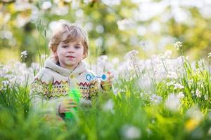 glad liten pojke i vårträdgården med blommande vita blommor foto
