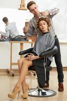frisör som gör frisyr för ung vacker kvinna foto