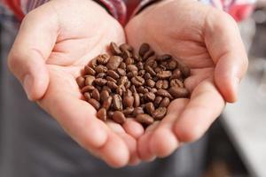 närbild av personen som håller kaffebönor