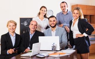 avslappnade anställda som sitter vid skrivbordet foto