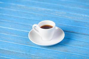 kopp kaffe på träbord. foto