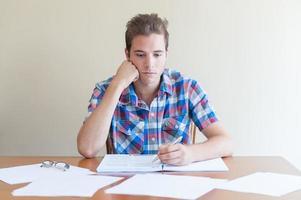 ung vuxen studerar, känner sig frustrerad, på ett rörigt skrivbord foto