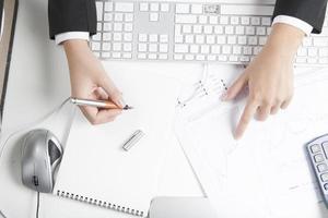 aktiemäklare som arbetar vid skrivbordet, anteckningsblock foto