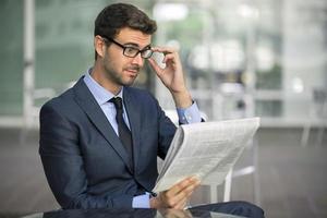 porträtt av förvånad affärsman med glasögon som läser tidningen foto