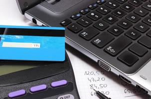 betalningsterminal med kontaktlös kreditkort, bärbar dator och finansiella beräkningar foto