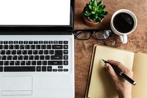 bärbar dator och kopp kaffe med handen arbetar foto