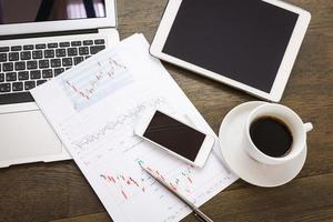 bärbar dator, surfplatta, smartphone och kaffekopp med finansiella foto