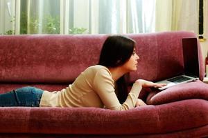 ung vacker kvinna som ligger på soffan med laptop foto