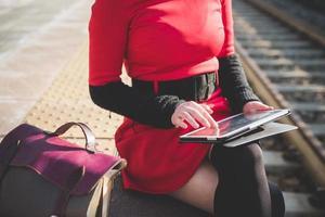 närbild händer kvinna med surfplatta på stationen foto