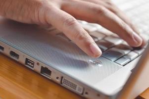 närbild av fingrarna vidrör tangentbordet på träbord foto