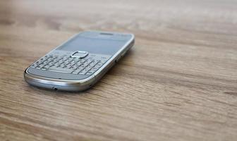 silver mobiltelefon på träbordet foto