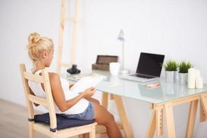 blond kvinna som läser några anteckningar i sitt arbetsområde foto