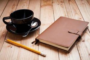 kaffekopp med anteckningsbok och penna foto