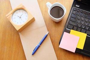 anteckningsbok och bärbar dator på träbord med kaffe foto