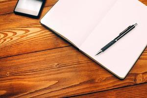 bord med anteckningsbok, smartphone och penna foto