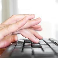 händerna på datorns tangentbord foto