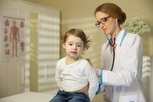 söt liten flicka och läkare foto