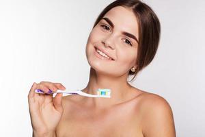 leende flicka med tandkräm på borsten foto