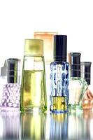 många flaskor med olika färger isolerad parfym. foto