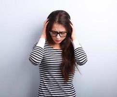företag olycklig ung kvinna med huvudvärk håller huvudet handen foto