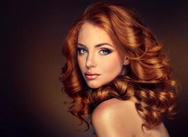 tjejmodell med långt lockigt rött hår. foto