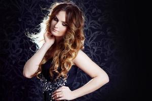 vacker flicka med långt brunt lockigt hår, mörk bakgrund foto
