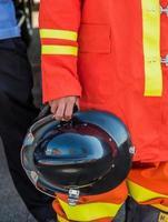 brandman håller sin hatt foto