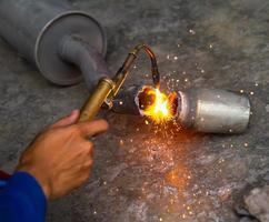 arbetare svetsar avgasrör av metall med gnistor foto