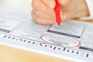 hand med röd penna markering jobb i tidningen foto