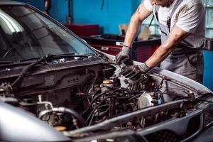 mekaniker som underhåller bilmotorn foto