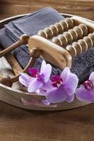 bricka med handduk och orkidéblommor för avkoppling och massage foto