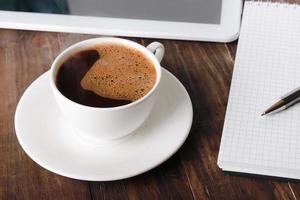 kopp kaffe, tablett och anteckningsbok foto