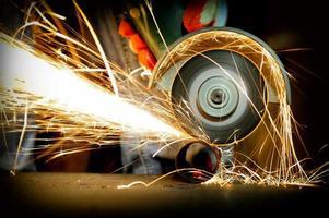 arbetare skärande metall med kvarn foto