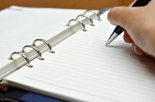 hand med en penna som skriver på vitt papper foto