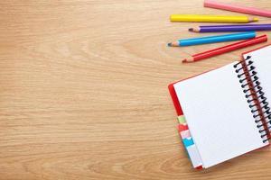 kontorsbord med tomt anteckningsblock och färgglada pennor foto