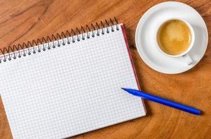 tomt anteckningsblock med penna och espresso foto
