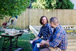 två snickare som pratar över kaffe foto