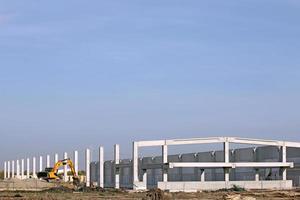 ny fabrikskonstruktionsplats med grävmaskin foto